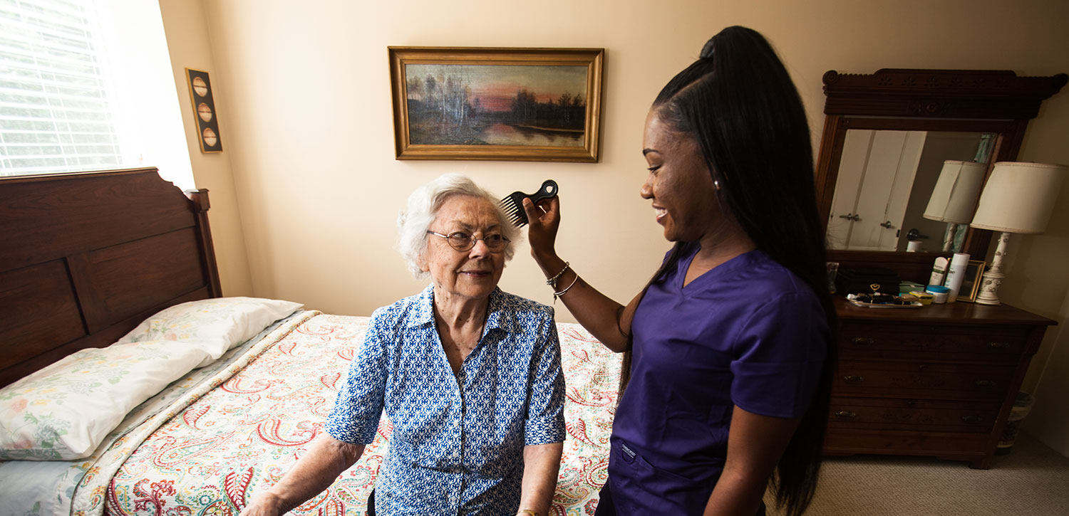 caregiver combing a senior woman's hair