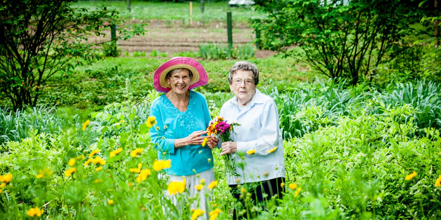 two senior women standing in a field of flowers
