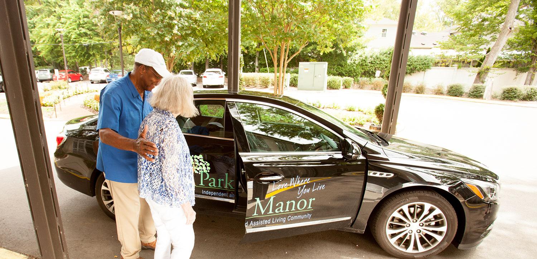 Park Manor employee helping a senior woman into a car