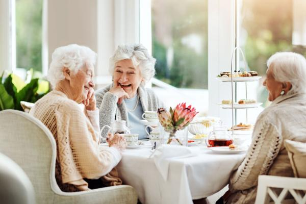Group of senior friends laughing and enjoying tea together
