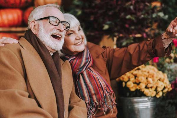 Senior couple bundled up outdoors with pumpkins in the background.